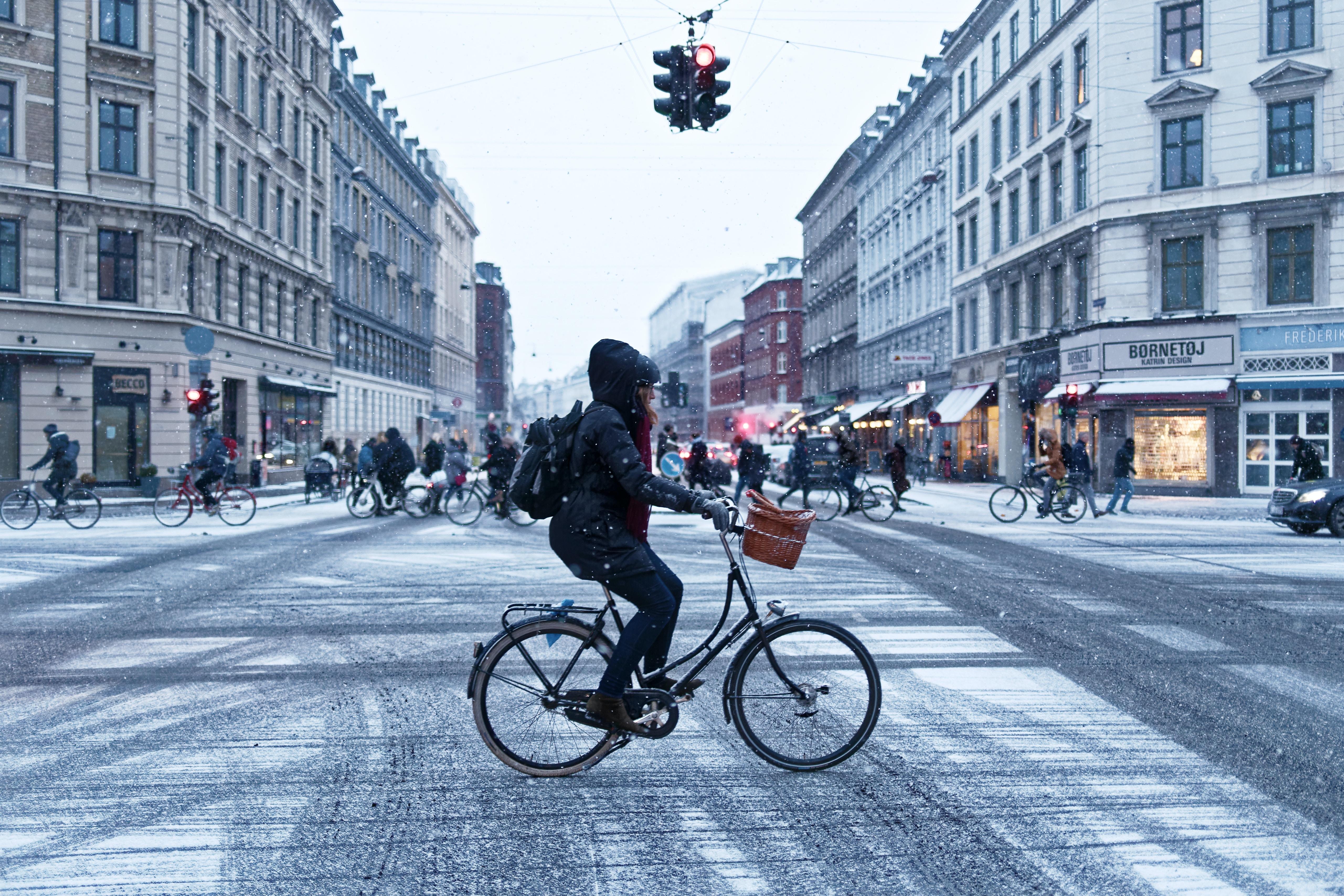 person cyclist near concrete buildings