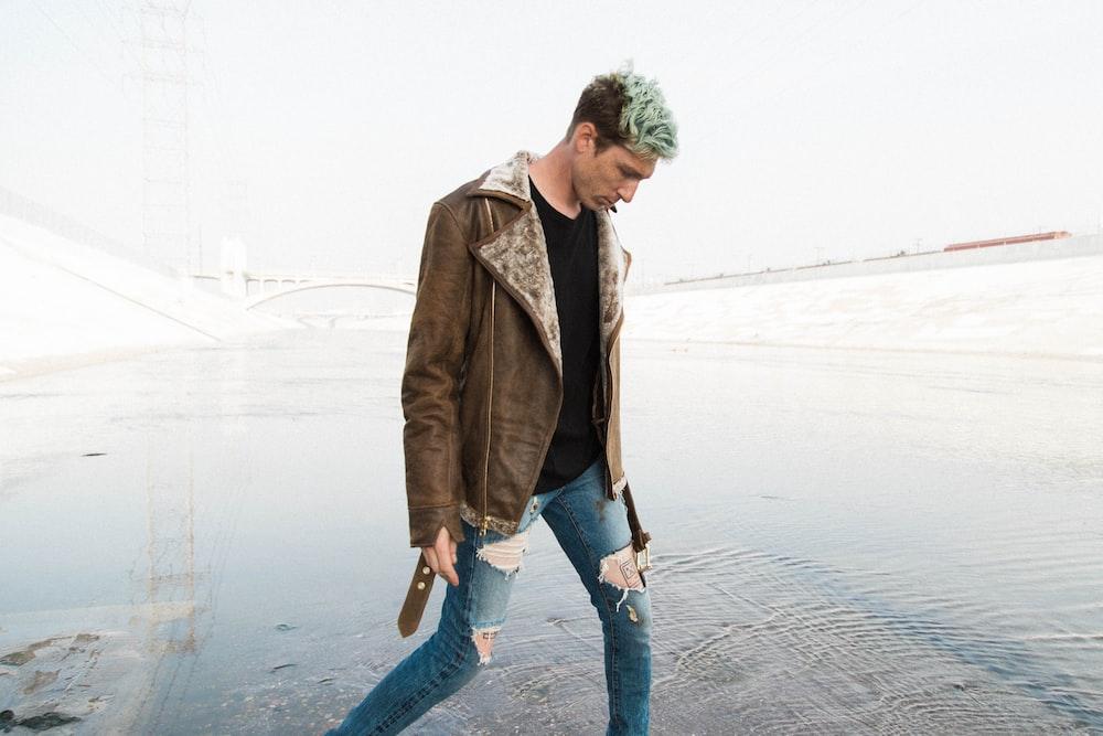 man in brown jacket walking near shore