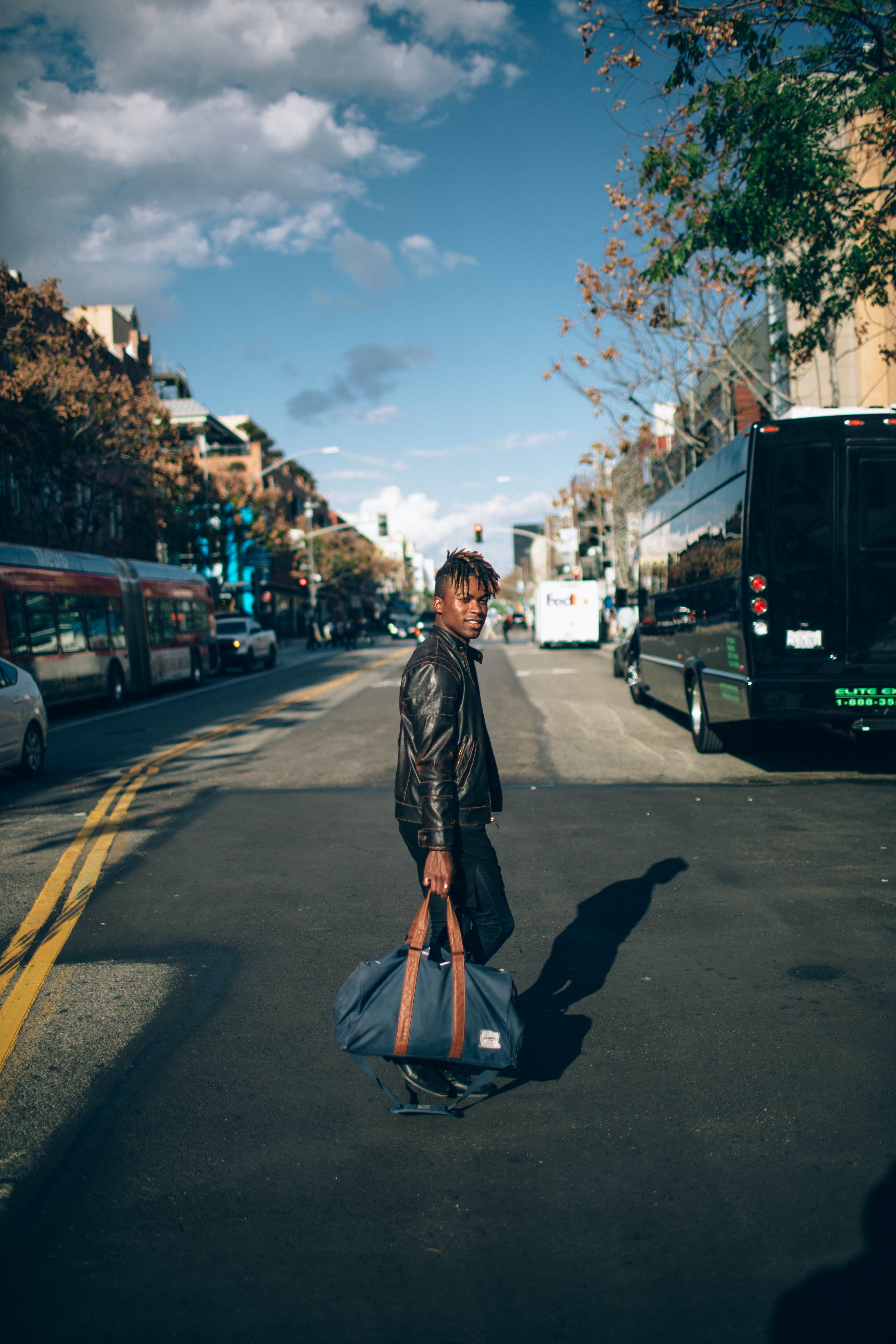 man walking on the street while carrying bag