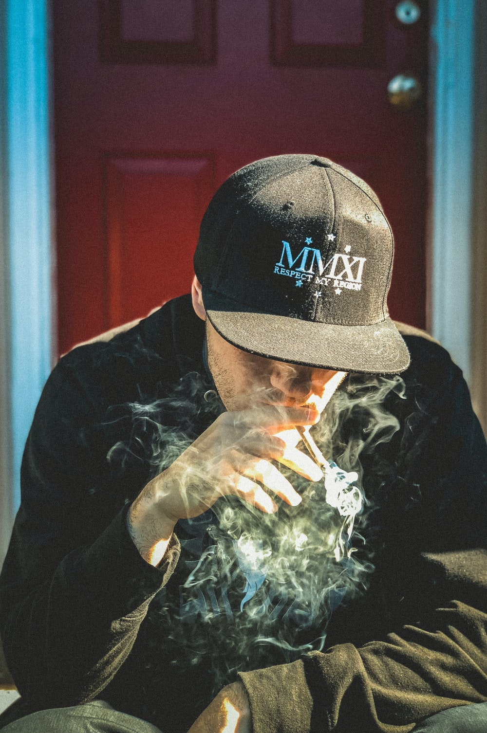 man in black cap and shirt sitting near door while smoking