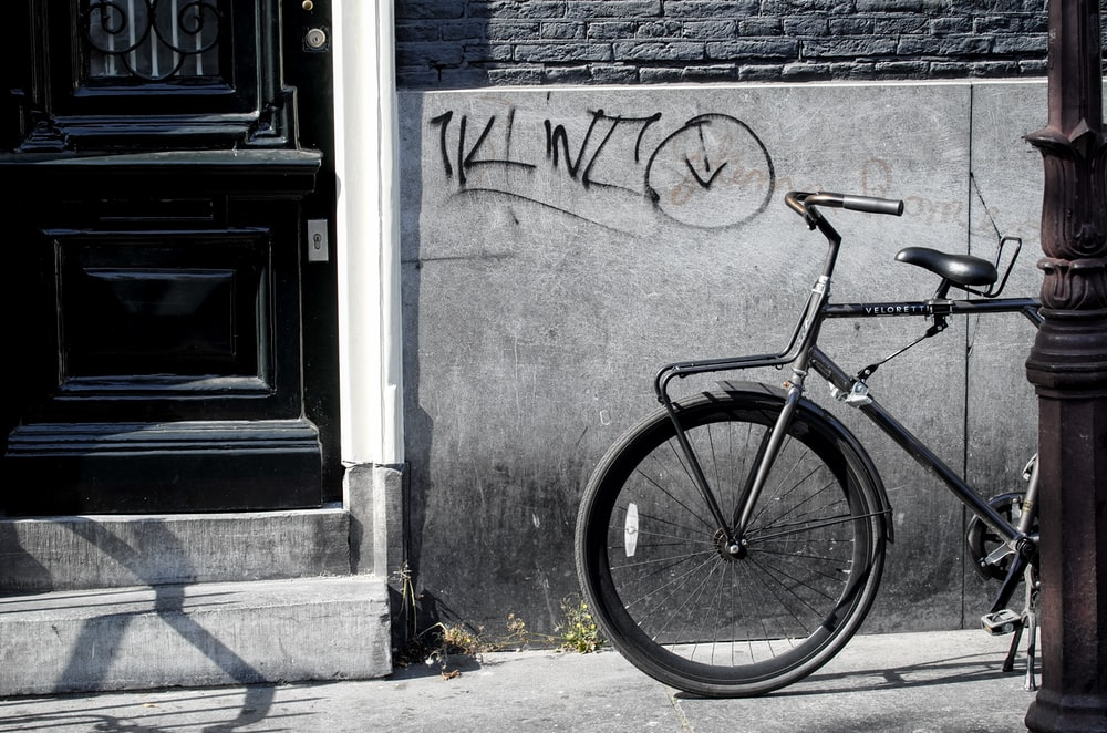 bicycle standing beside gray wall