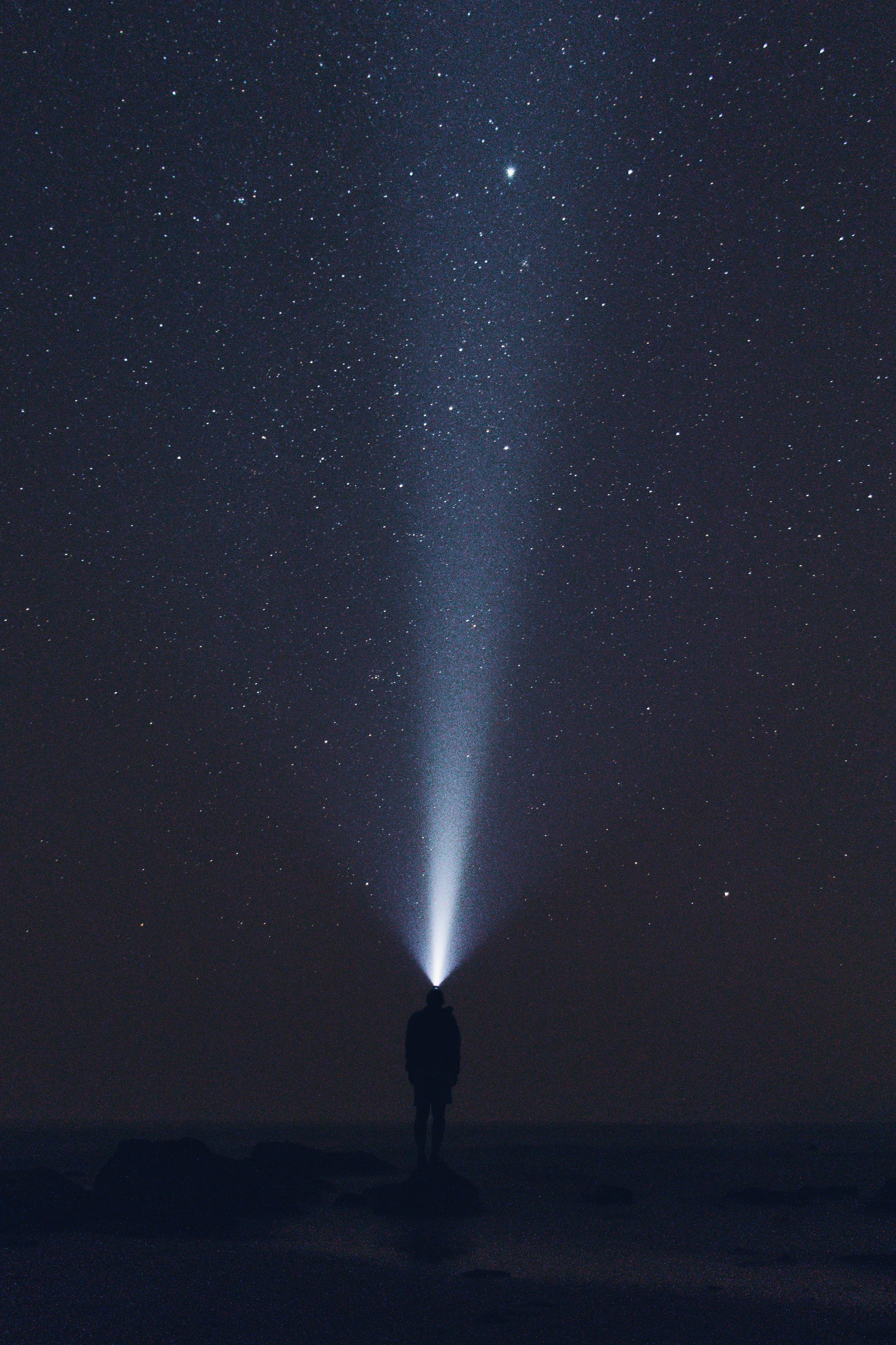 silhouette of man wearing headlamp during nighttime