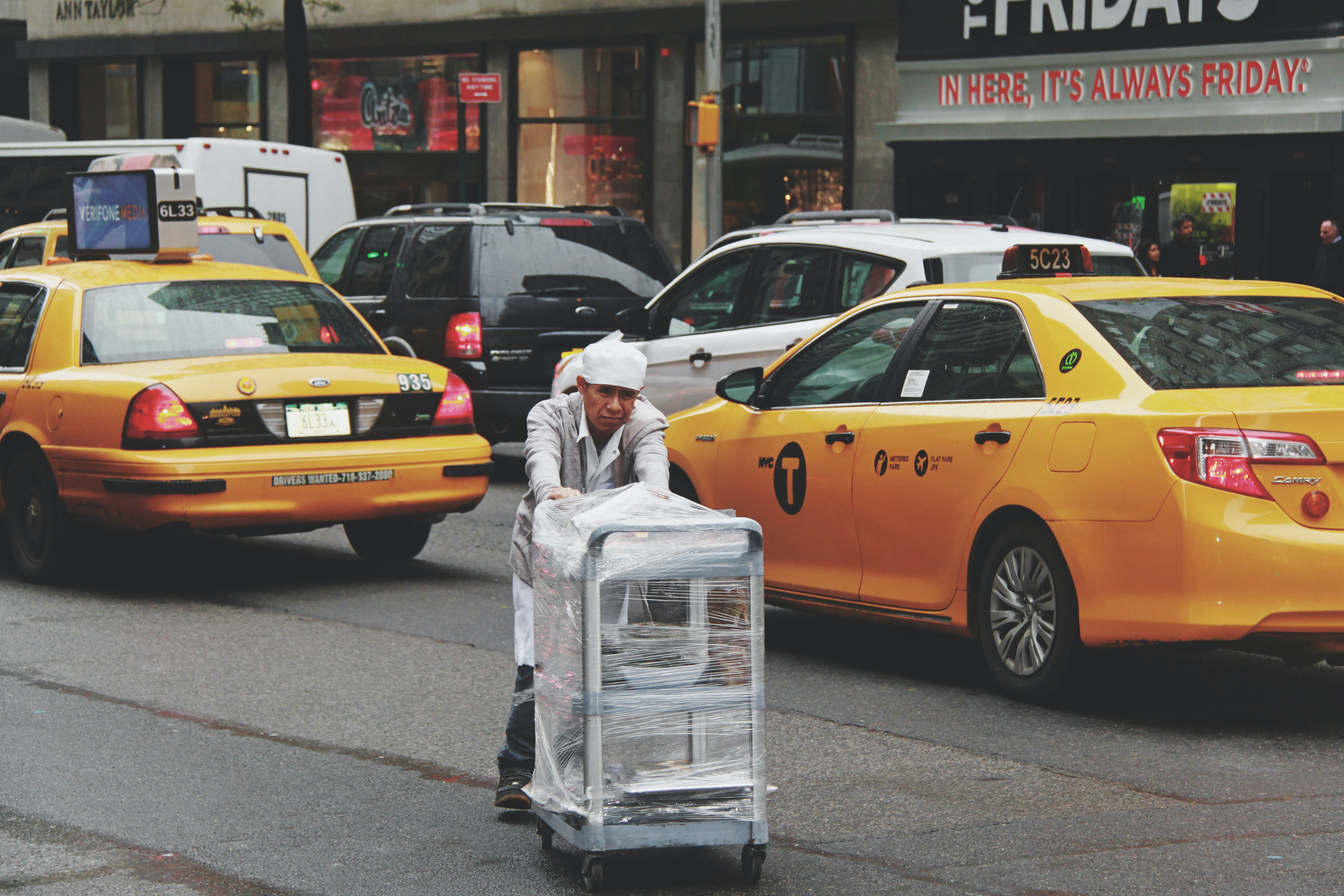 man pushing gray bus cart on road near two yellow taxi cabs