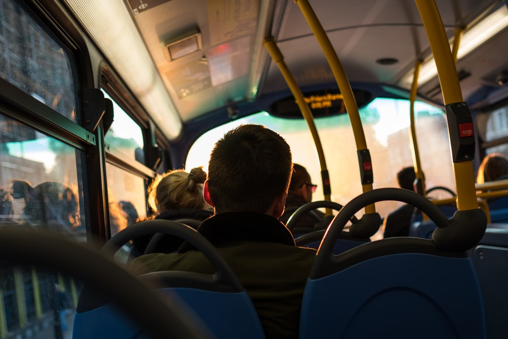 photo of man sitting inside bus