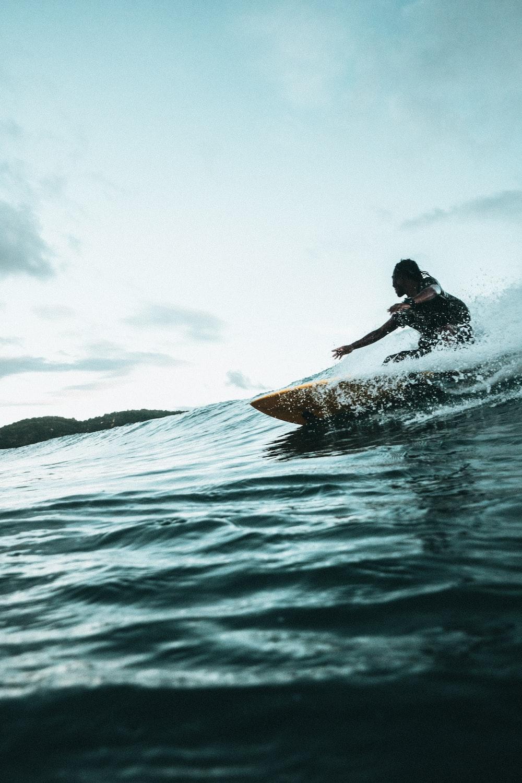 man surfboarding during daytime