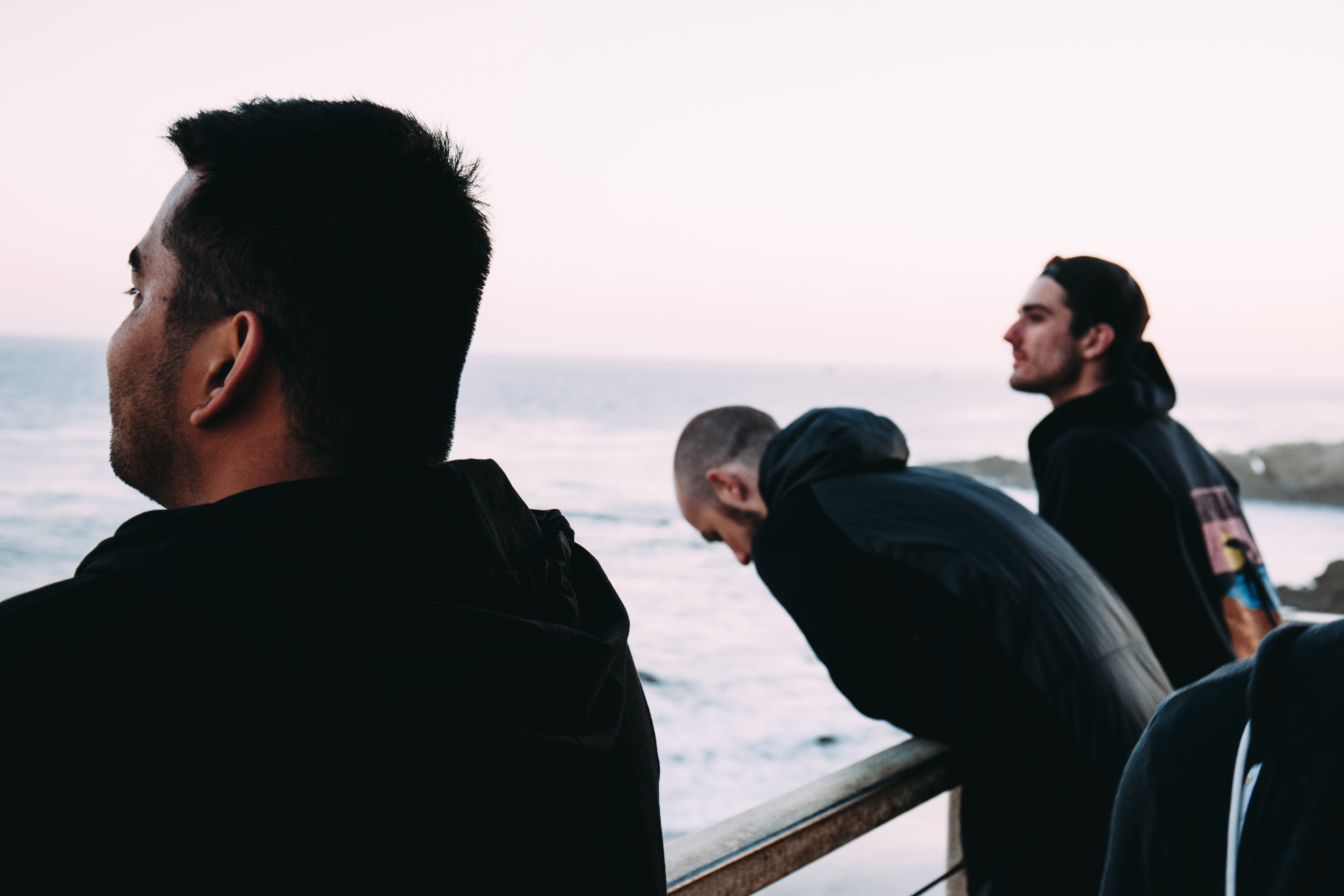 three men near rail near sea