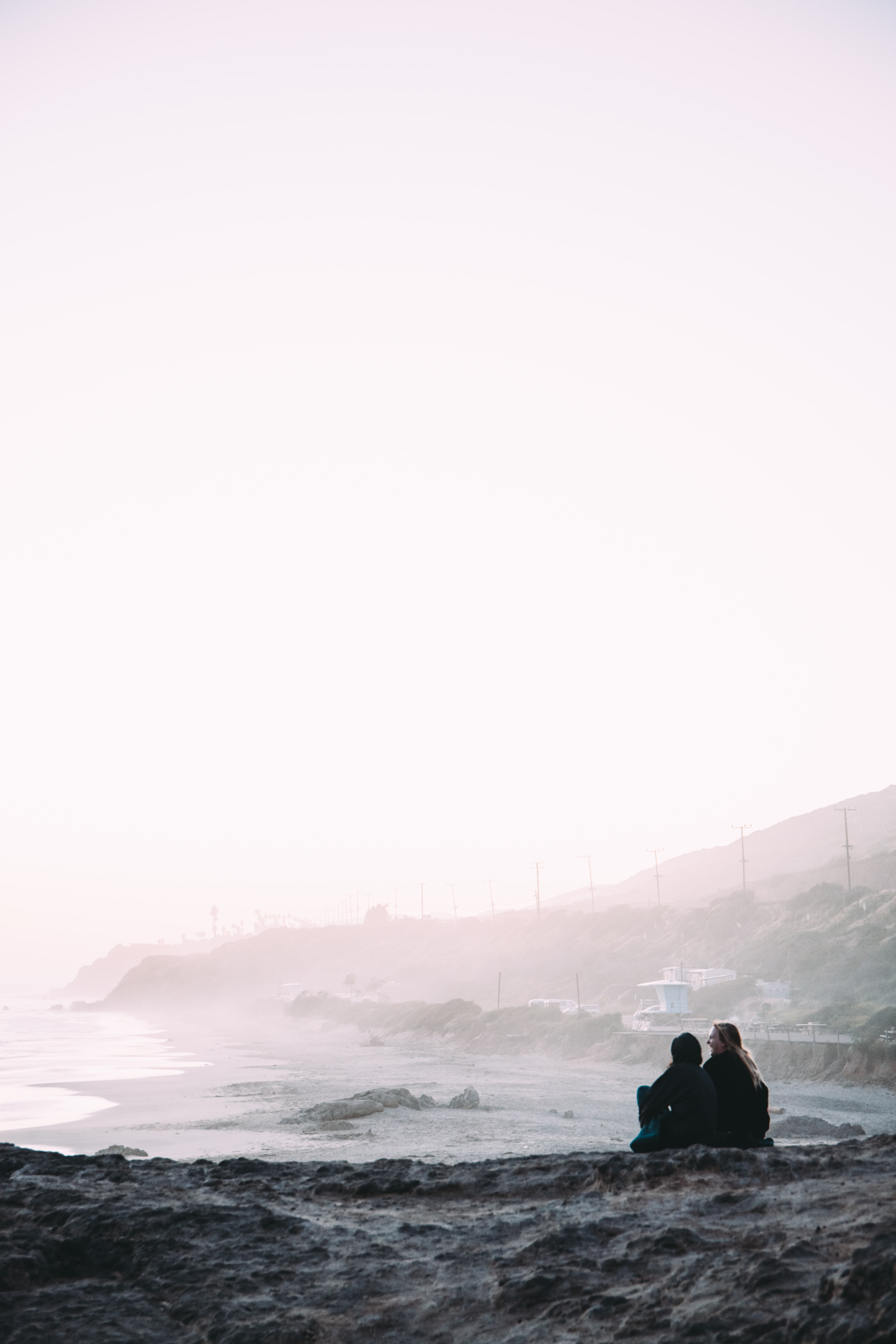 two person sitting beside shore