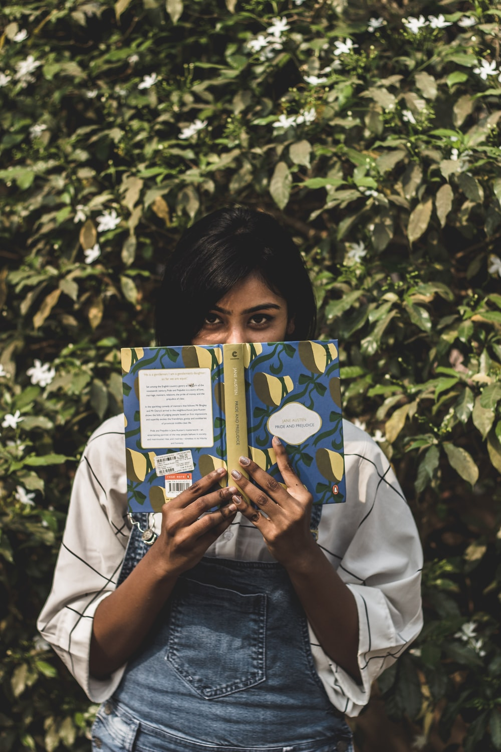 woman covering her face with book standing in front of green plants