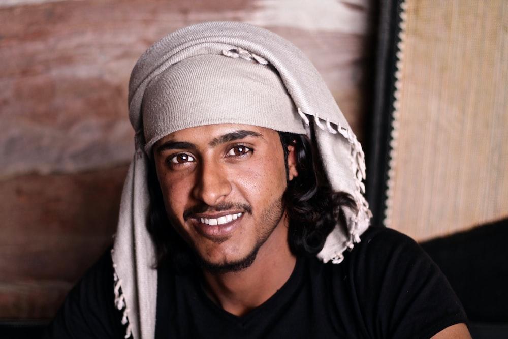 man wearing black crew-neck shirt and white headscarf