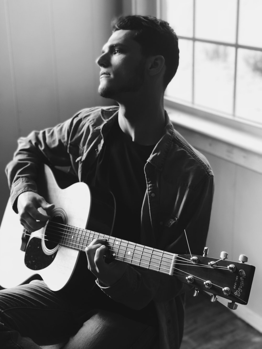 grayscale photography of man playing acoustic guitar