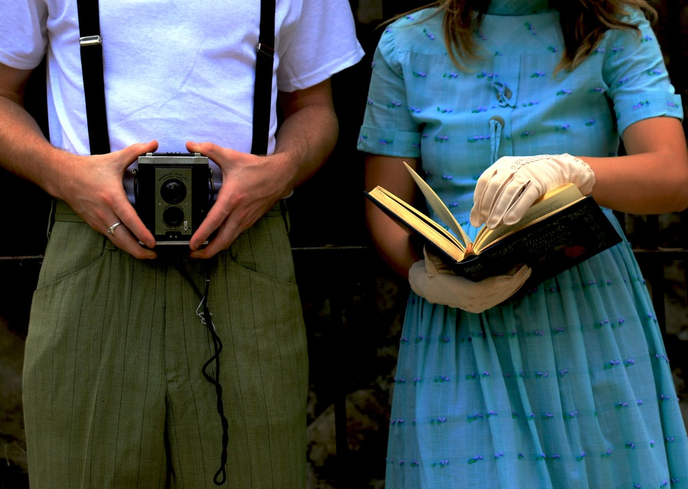 woman holding book while beside man holding vintage camera
