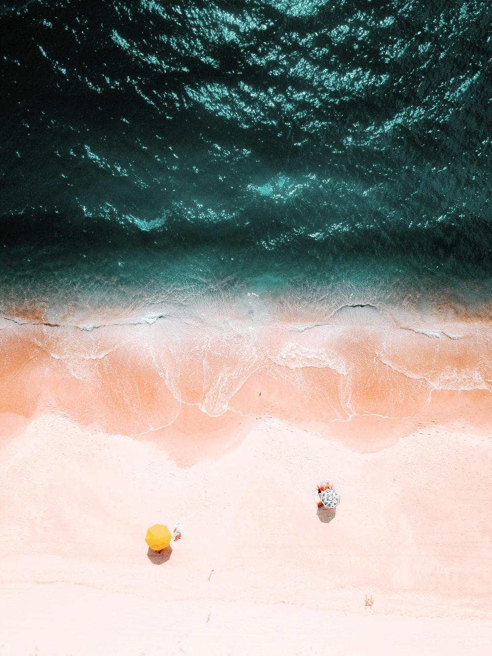 bird's eye view of two yellow and green umbrellas on beach