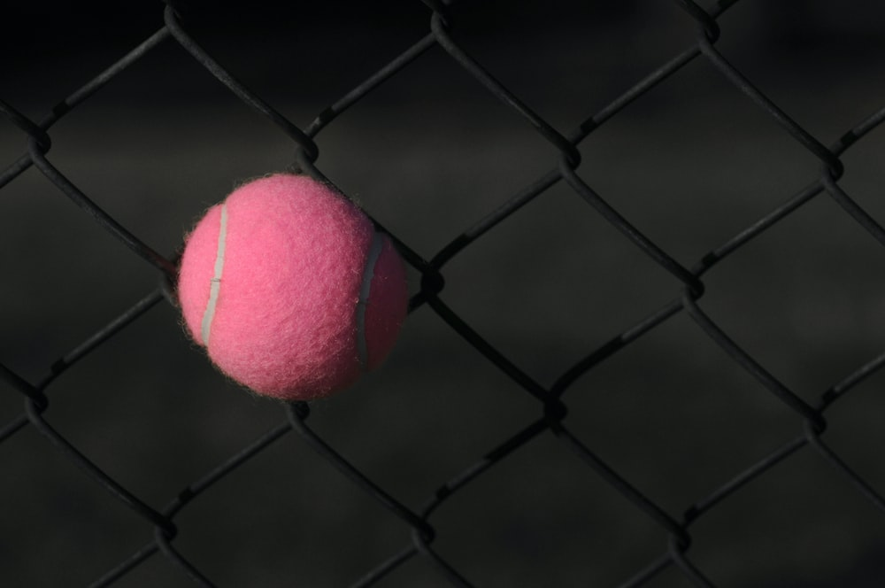 red tennis ball on gray steel fence