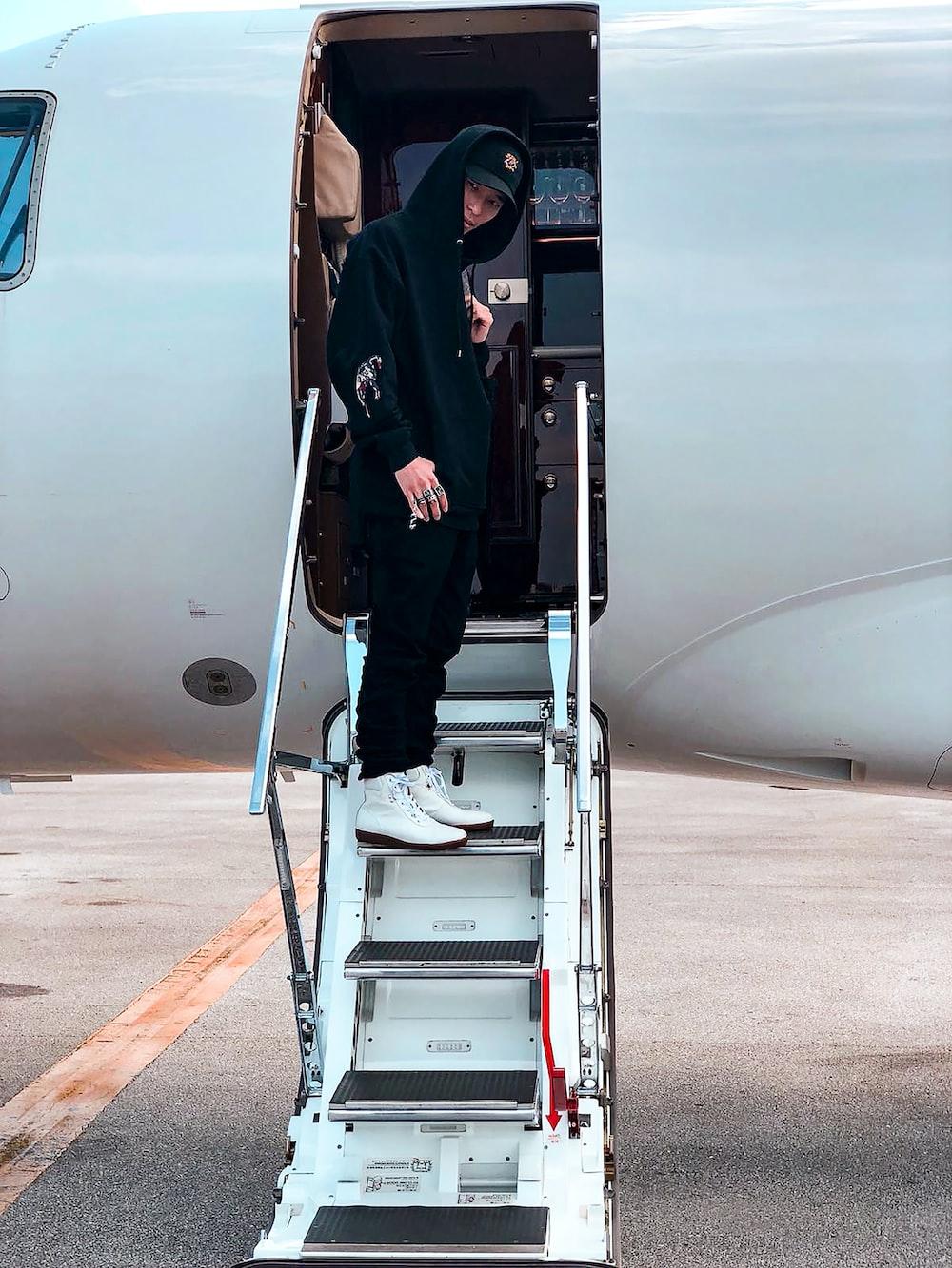 person stepping on passenger plane ladder