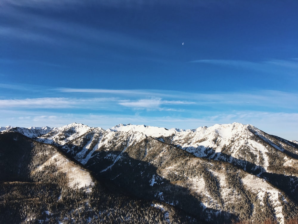 white and brown mountains under white clouds and blue sky during daytime