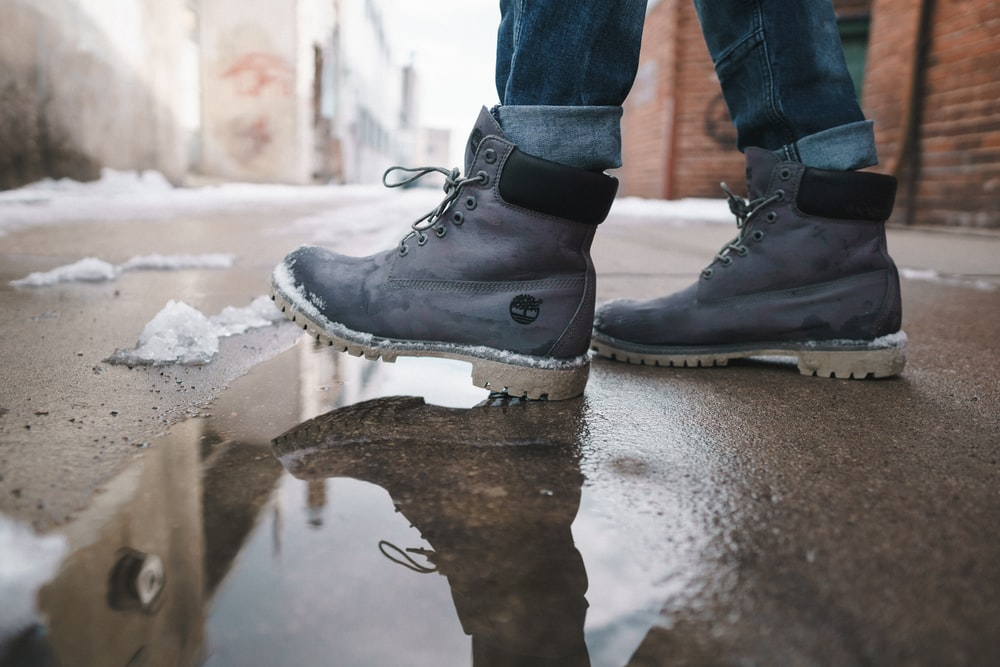 person wearing pair of gray Timberland work boots