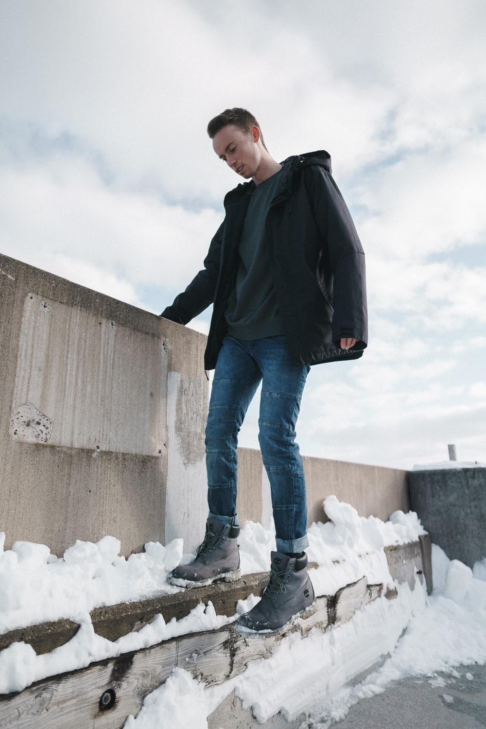 man standing beside wall cover by snow