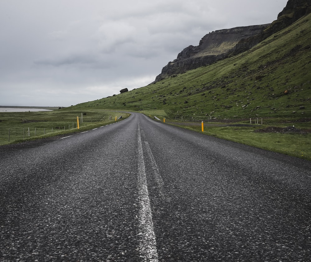 empty concrete road near mountain under cloudy sky at daytime