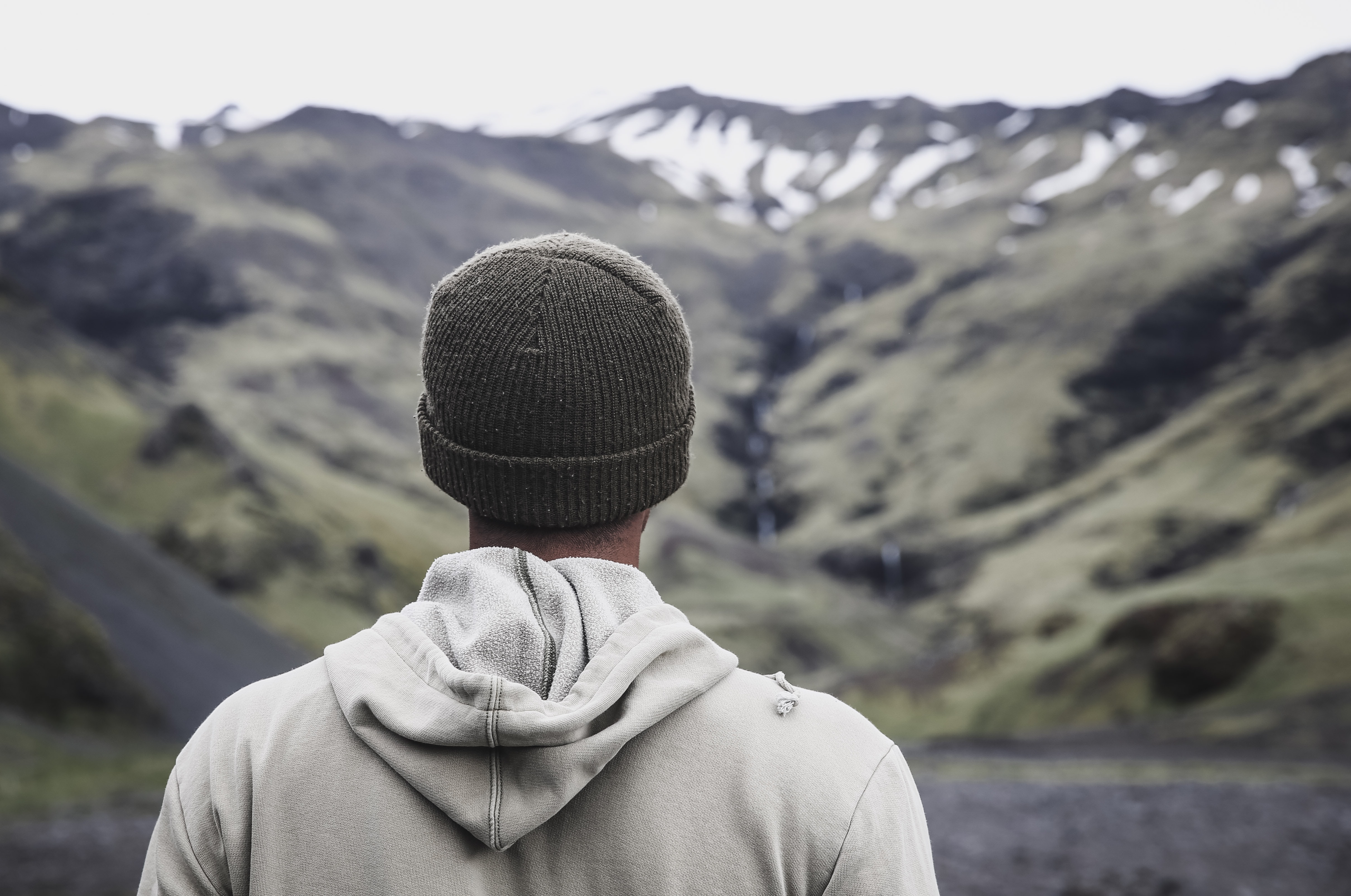 man wearing gray hooded jacket in front of mountain