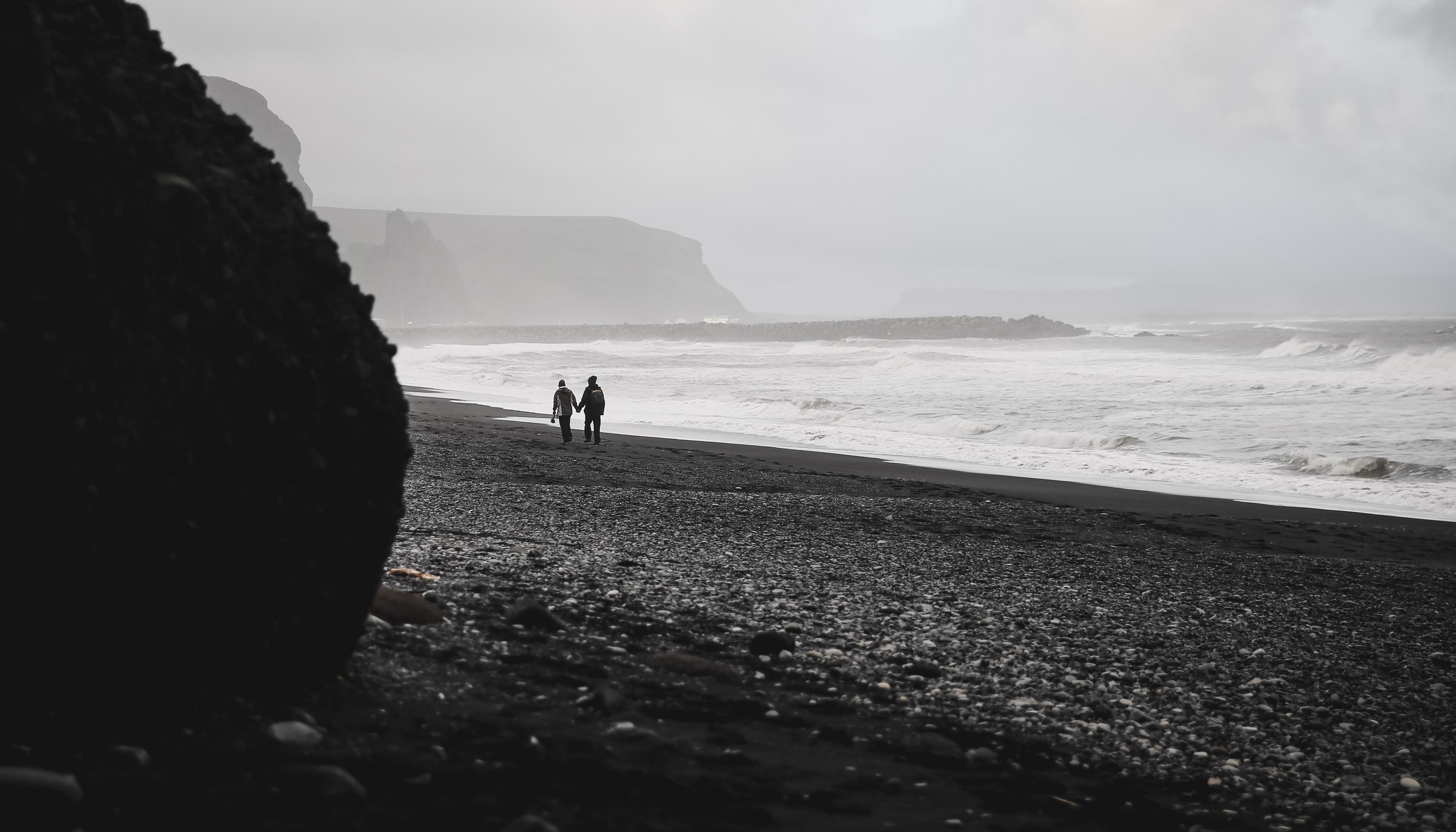 two person walking on shoreline near black rock
