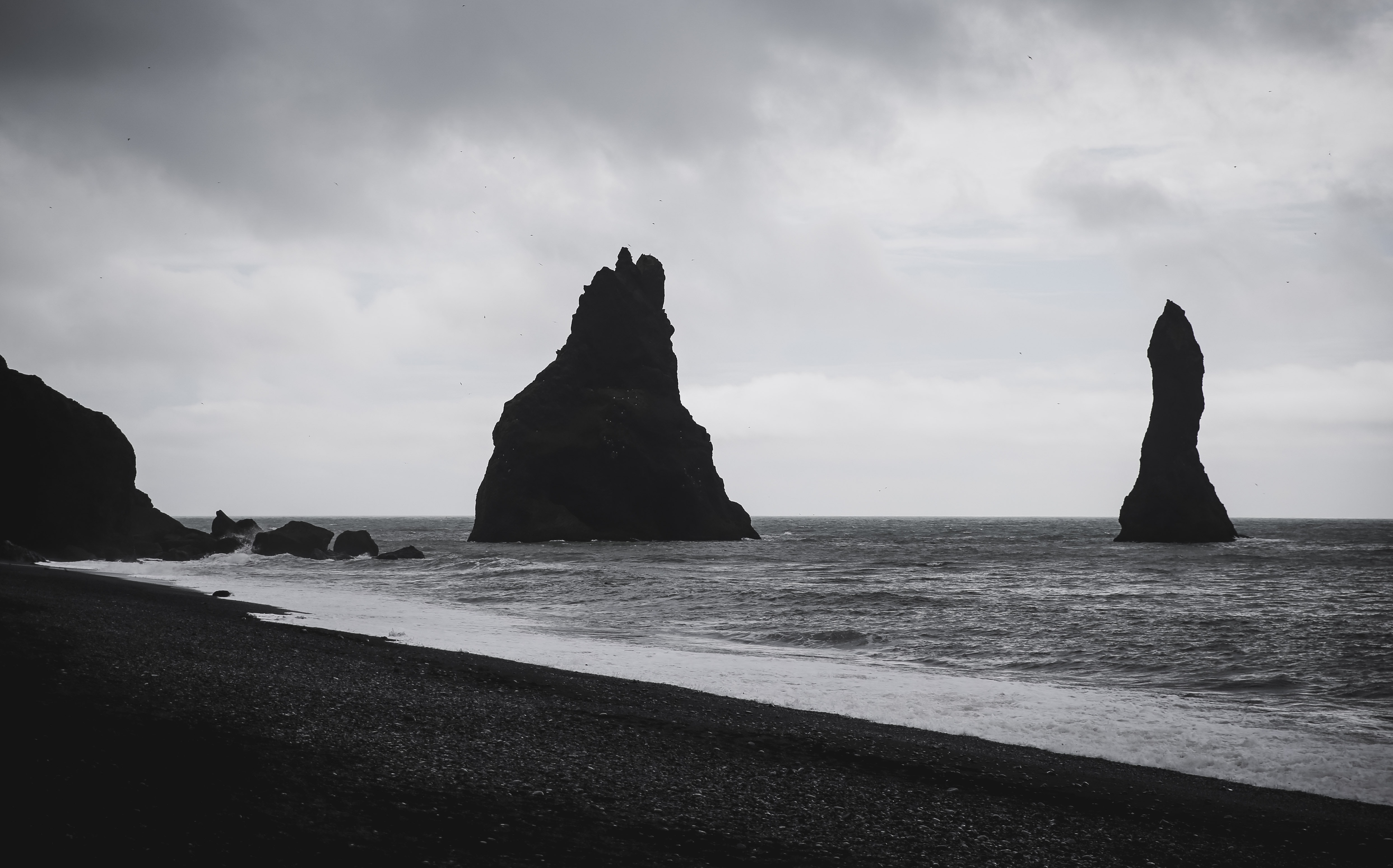 grayscale photography of rock formations on shore during daytime