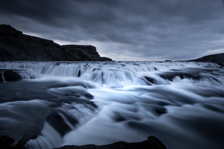 water flows near mountain under dark sky