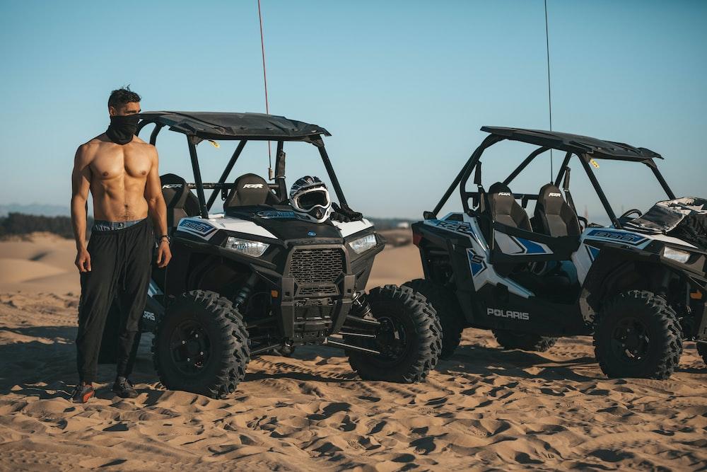 person standing beside black ATV
