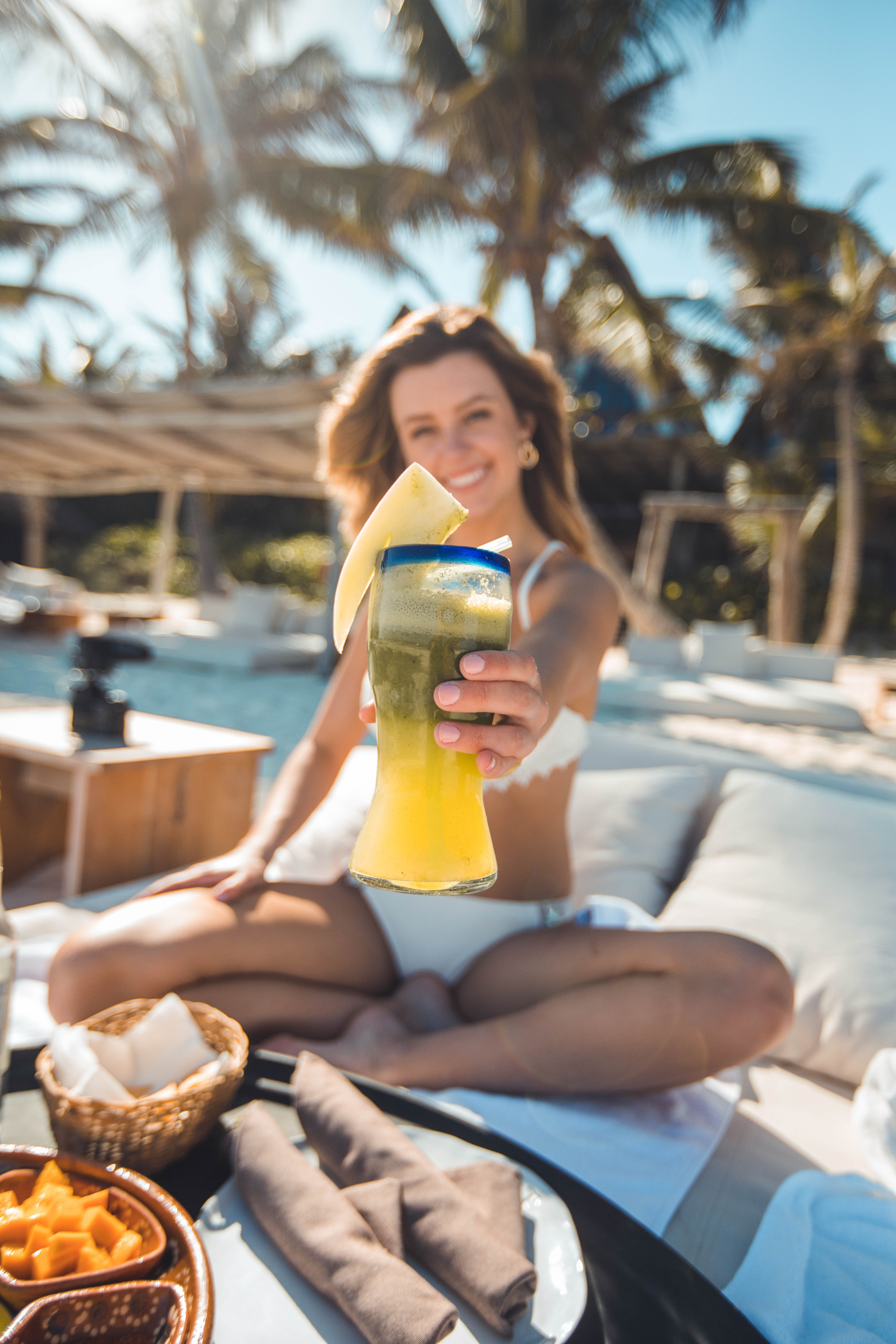 smiling woman holding clear glass cup filled with juice sitting on cushion