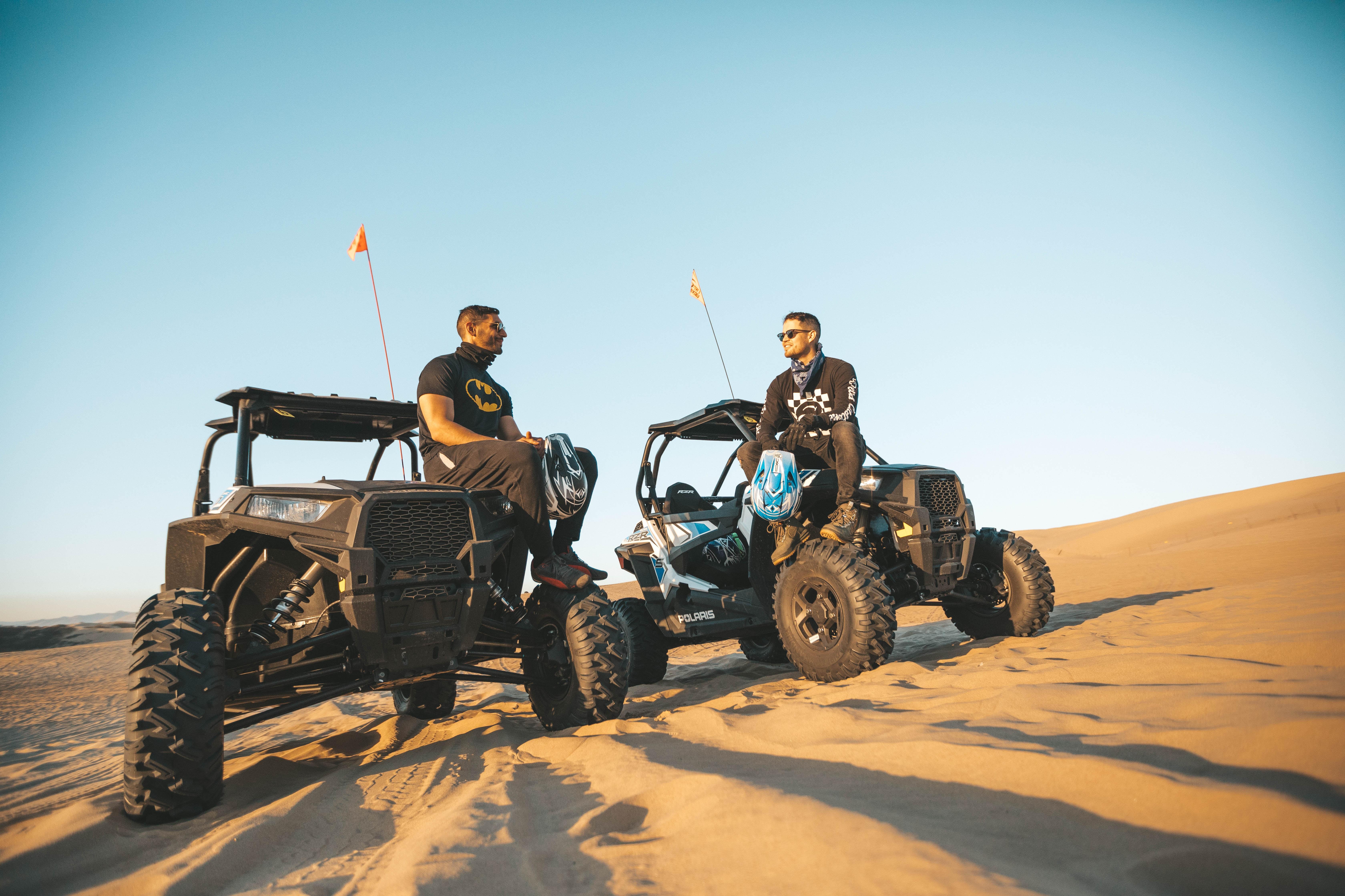 two men sitting on top of utility task vehicles on desert