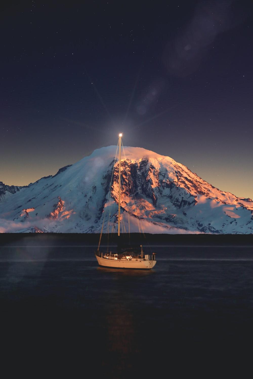 sailboat sailing near snowcapped mountains
