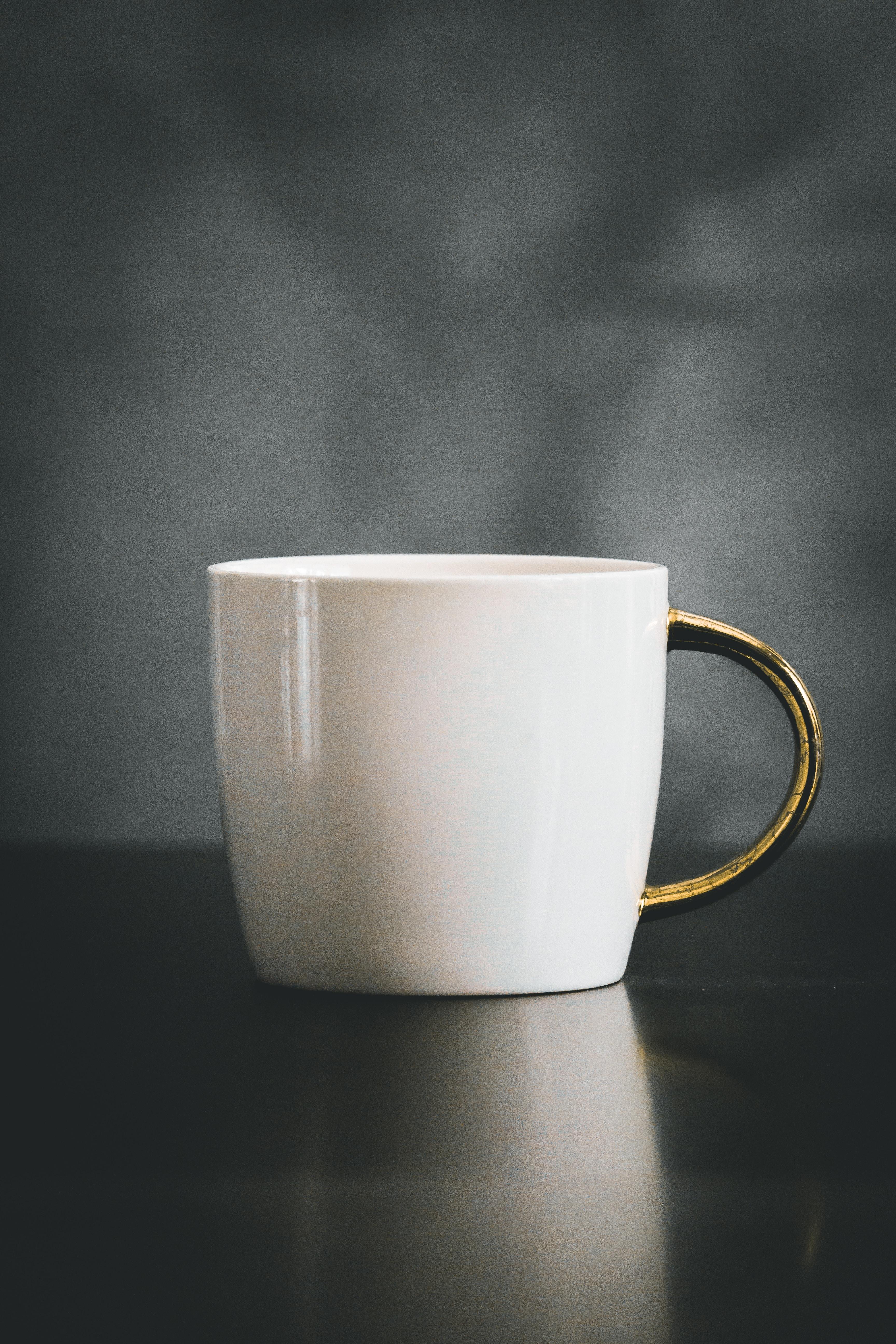 white and beige ceramic mug on black surface