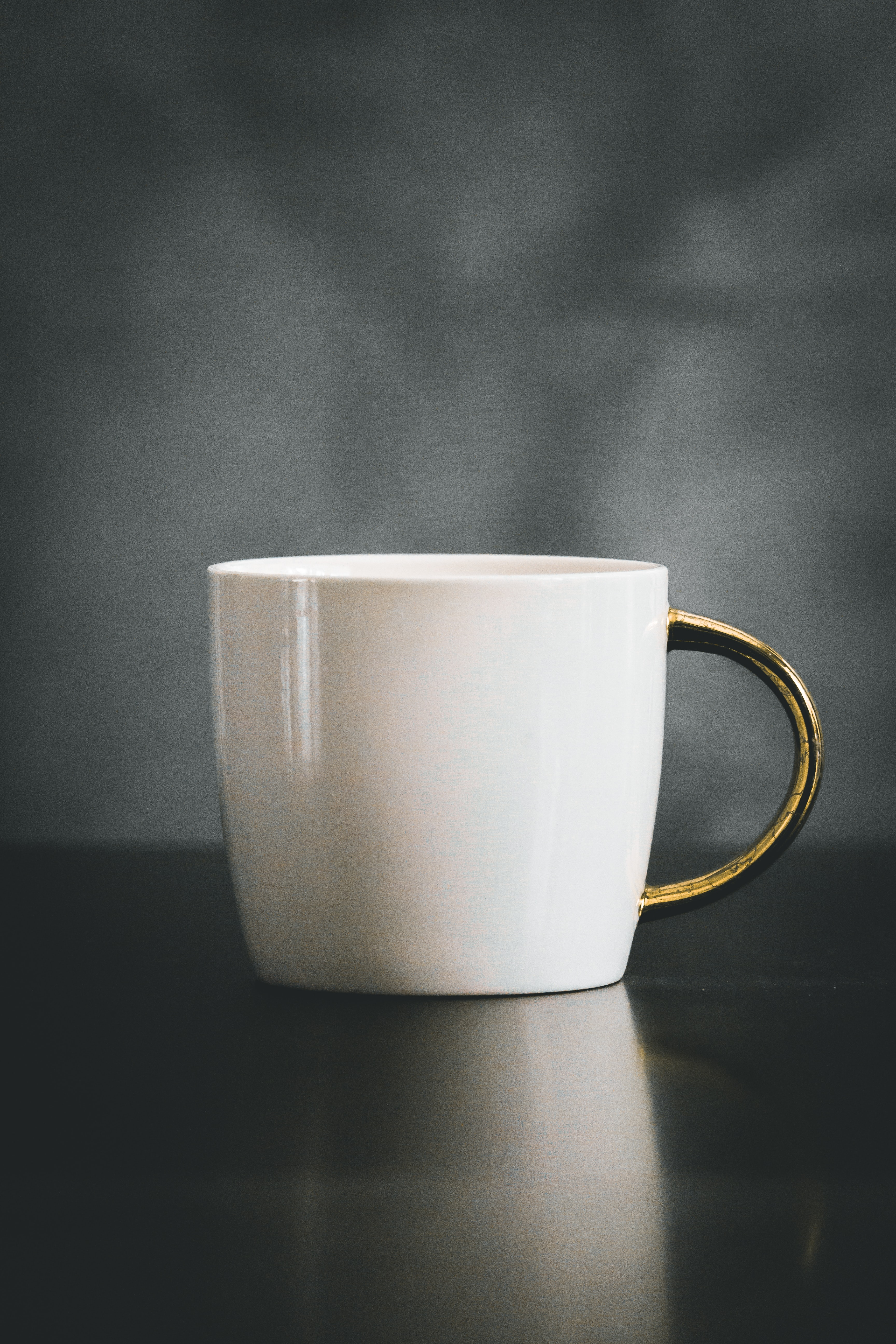 white and beige ceramic mug on black surface