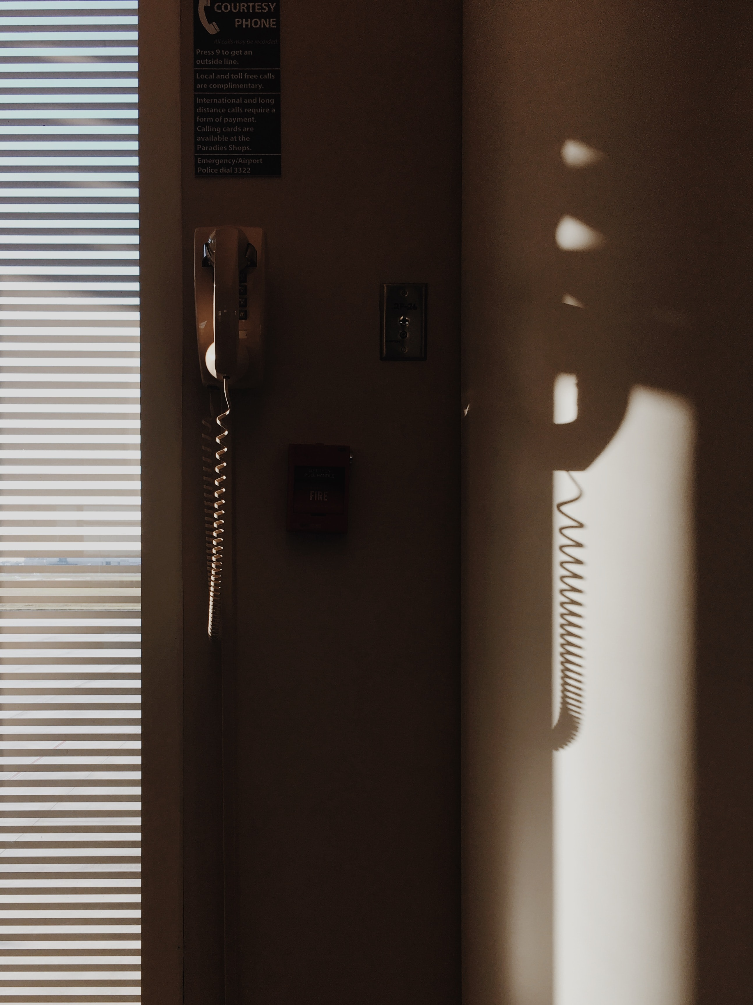 white corded telephone mounted on wall near window with window blinds