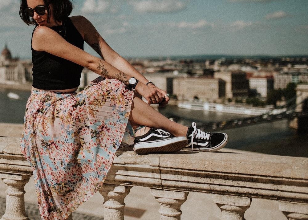 woman in sleeveless top,floral skirt and black Vans oldskool shoes