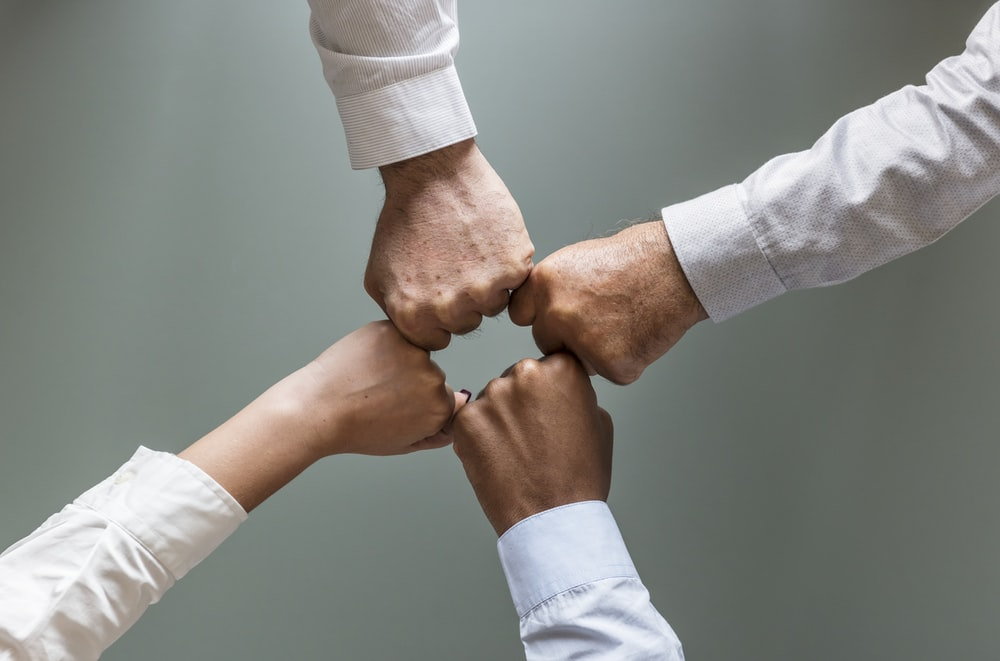 four person fist bumping