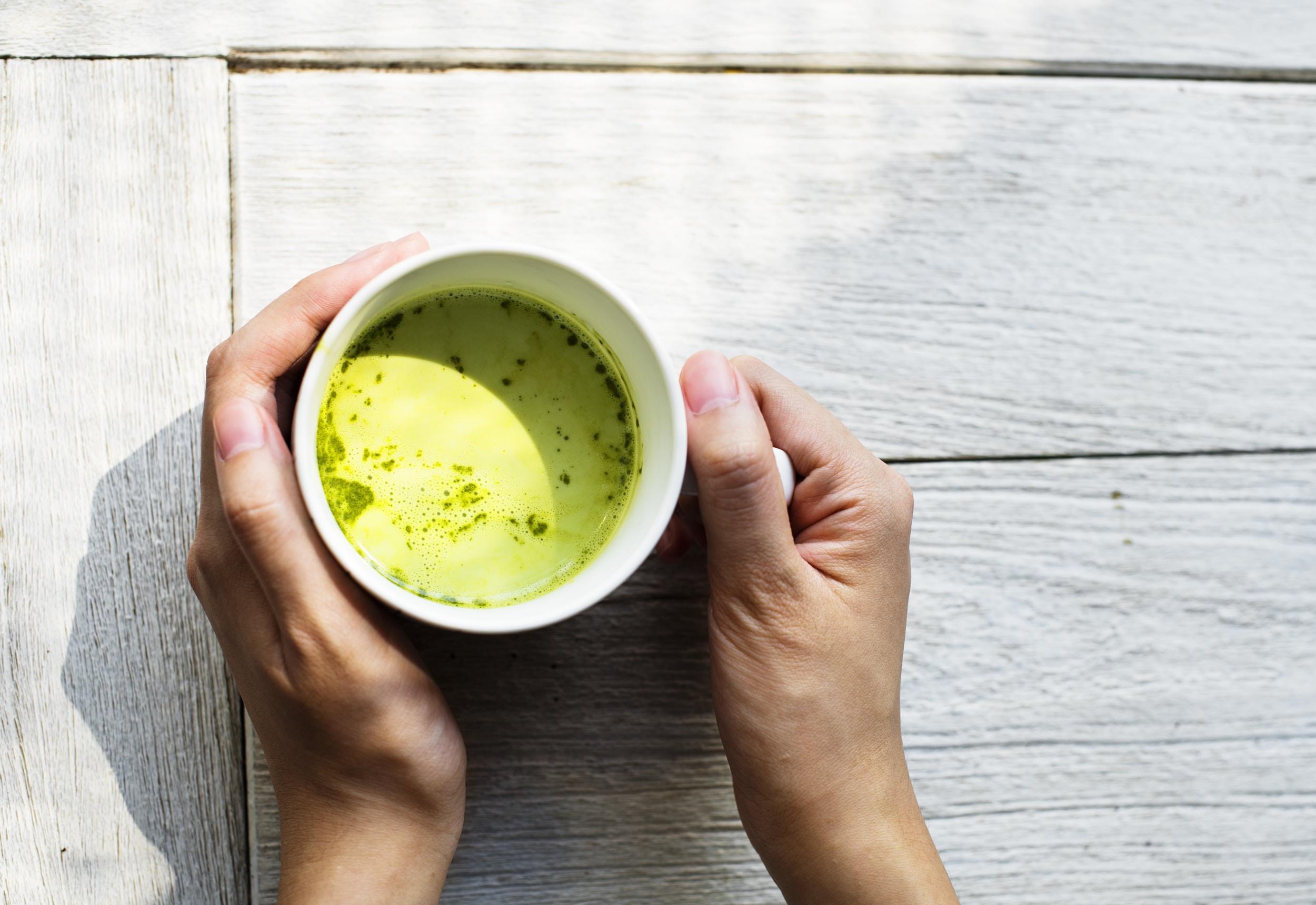 person holding mug with matcha tea