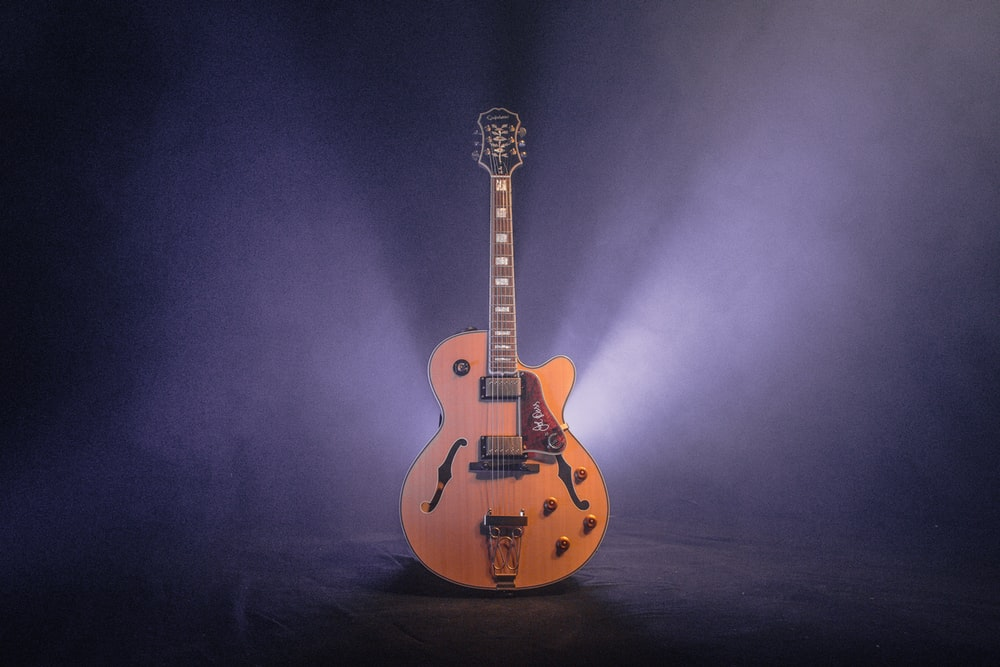 brown and black jazz guitar with dim light