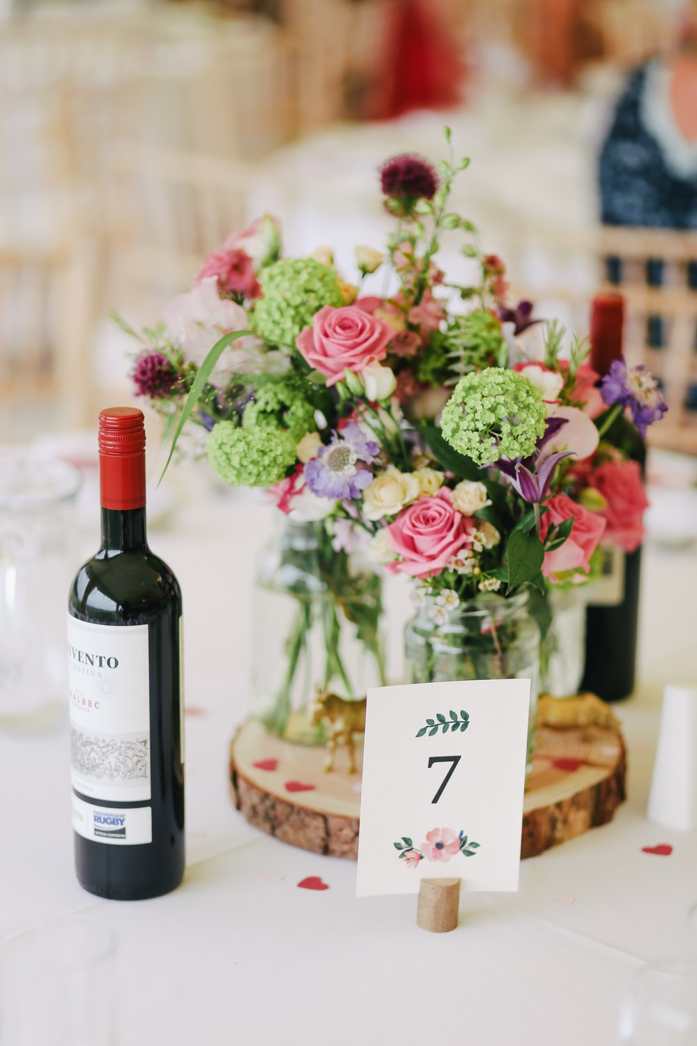 flower arrangement with wine bottle on the table