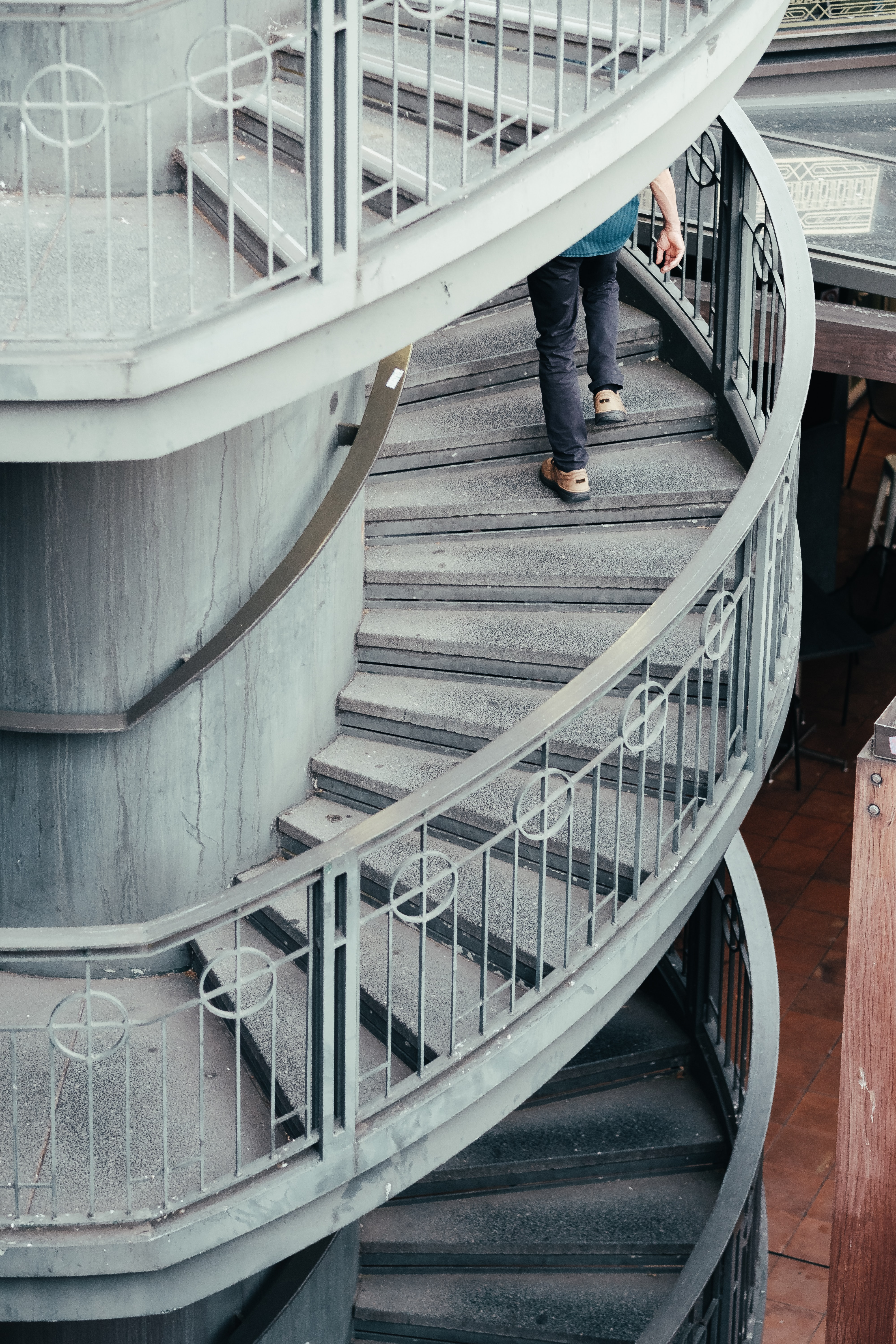 person walking on spiral staircase during daytime