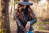 shallow focus photography of woman standing in front of tree while zipping her jacket