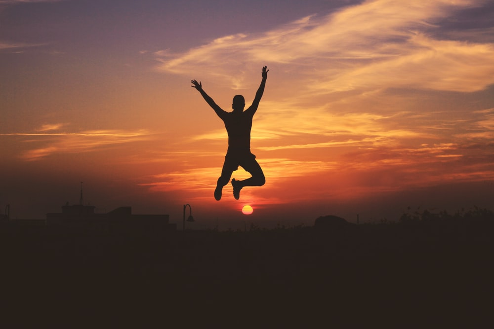 silhouette of man jumping raising both hands during golden hour