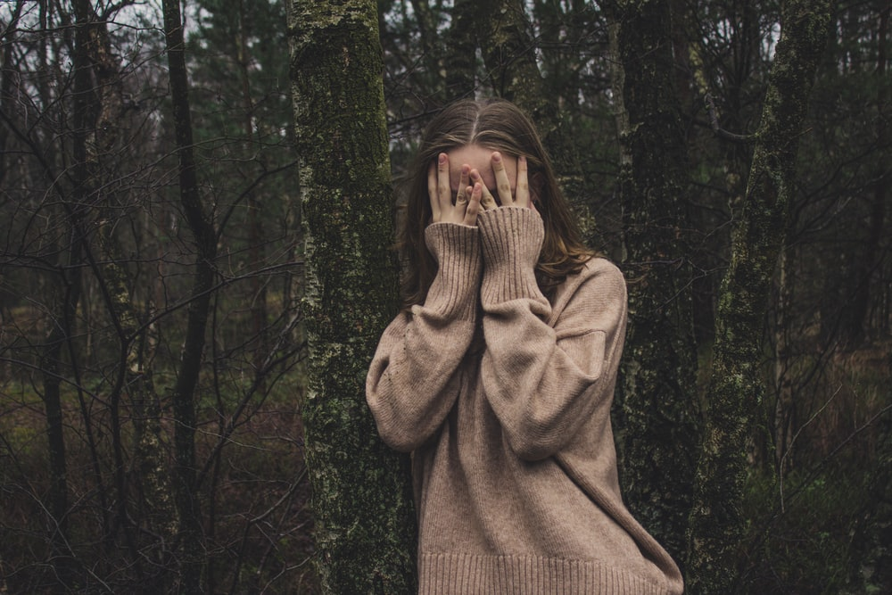 woman wearing brown sweater standing on forest