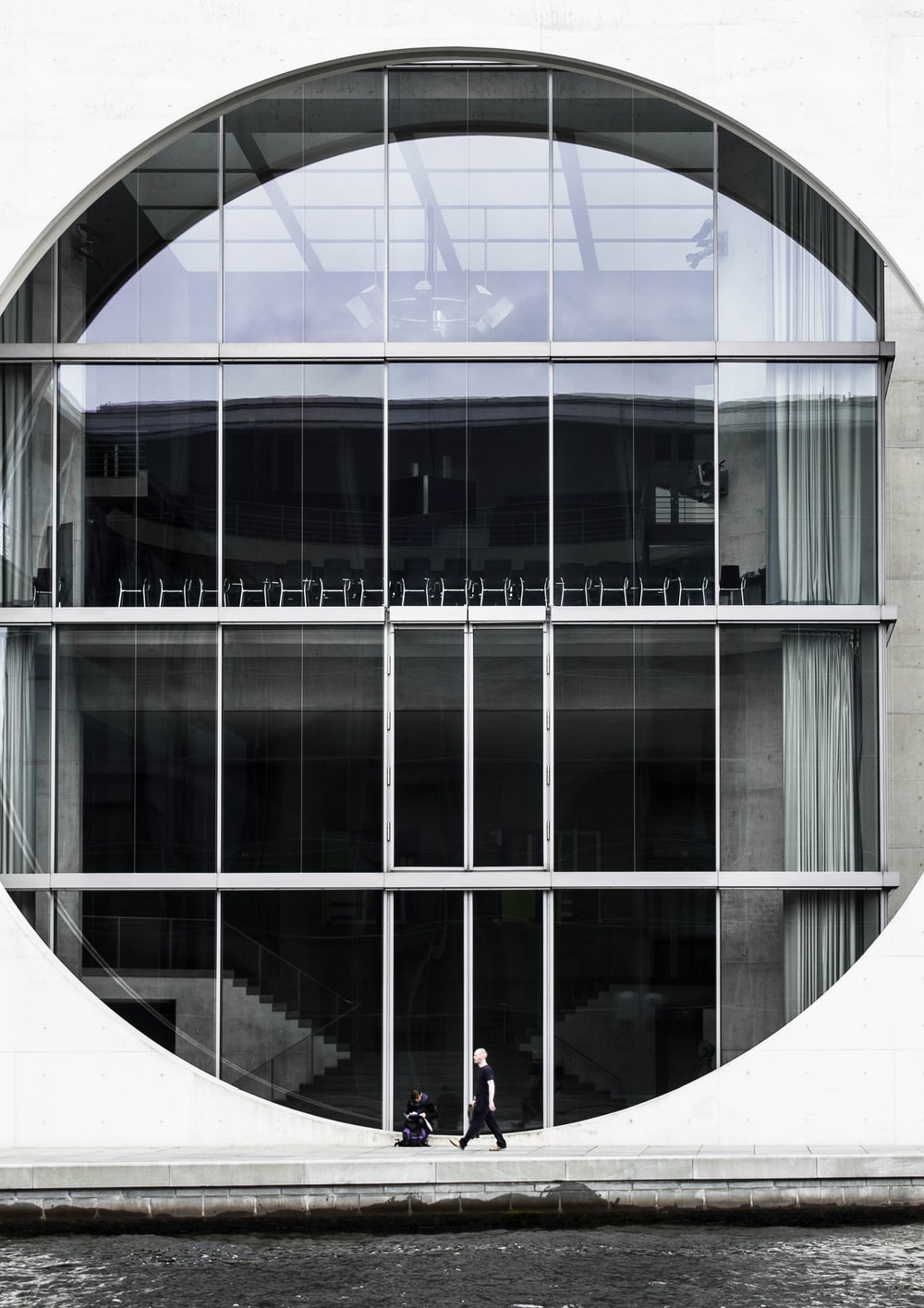 person beside clear glass building