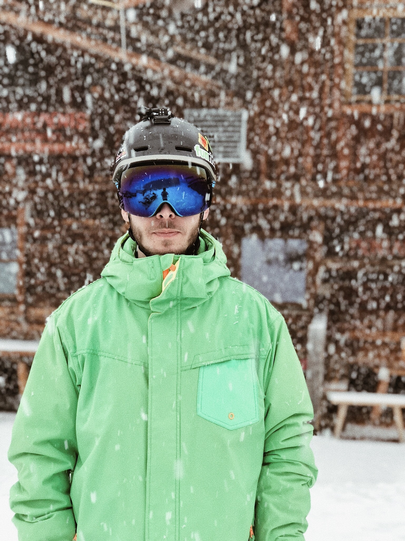 man in green zip-up hooded jacket black helmet and black goggles standing on snow during daytime