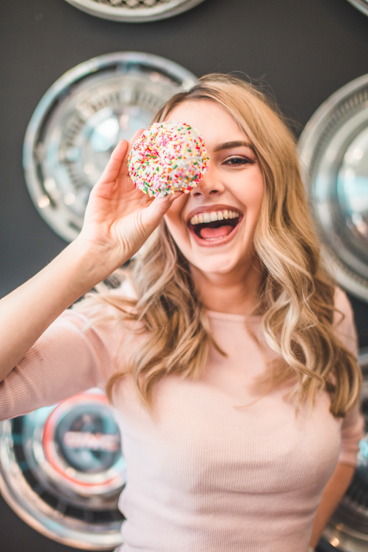 shallow focus photography of woman holding doughnut