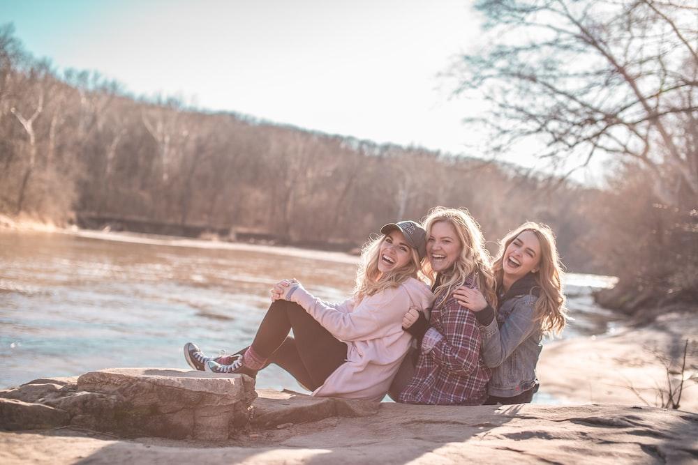 three women sitting on rock near body of water
