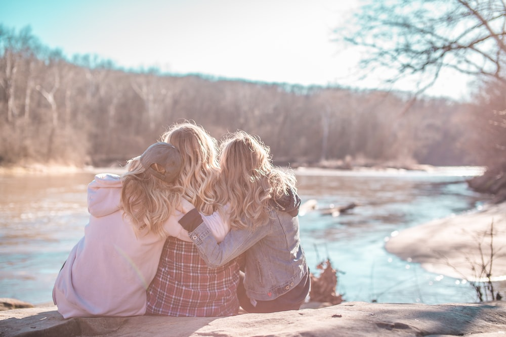 three women sitting on rock near body of water surrounded by trees during daytime