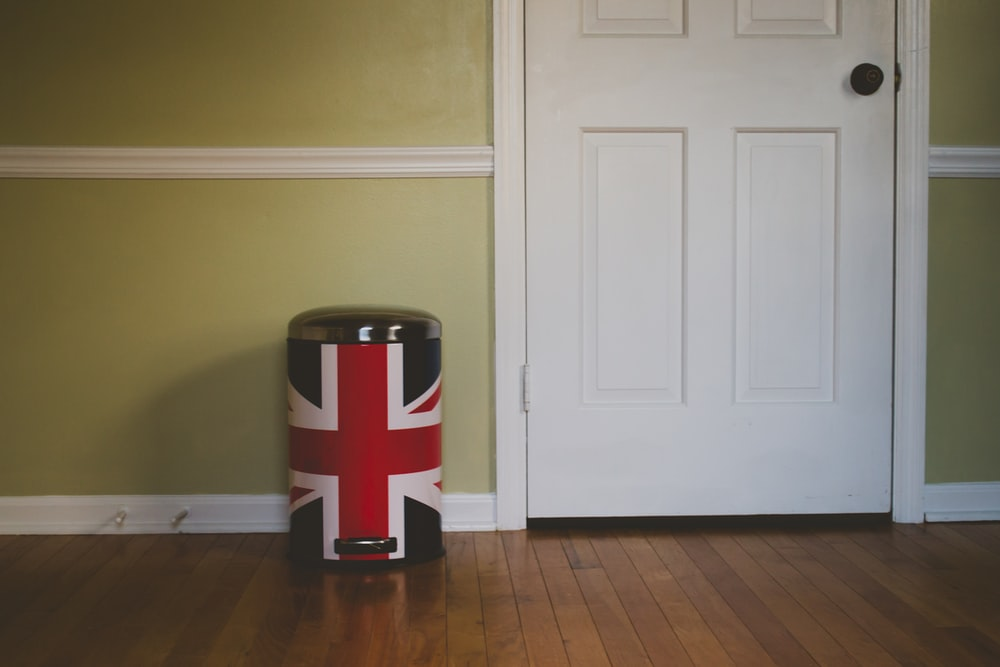 black and red UK flag pedal trash bin near white wooden door