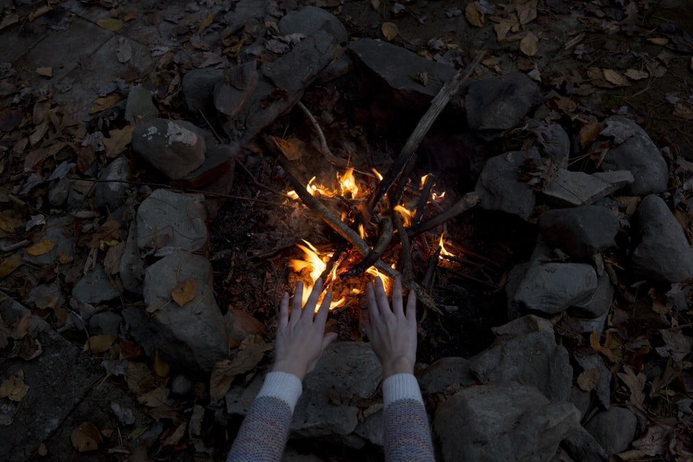 photography of person warming his/her hands at bonfire