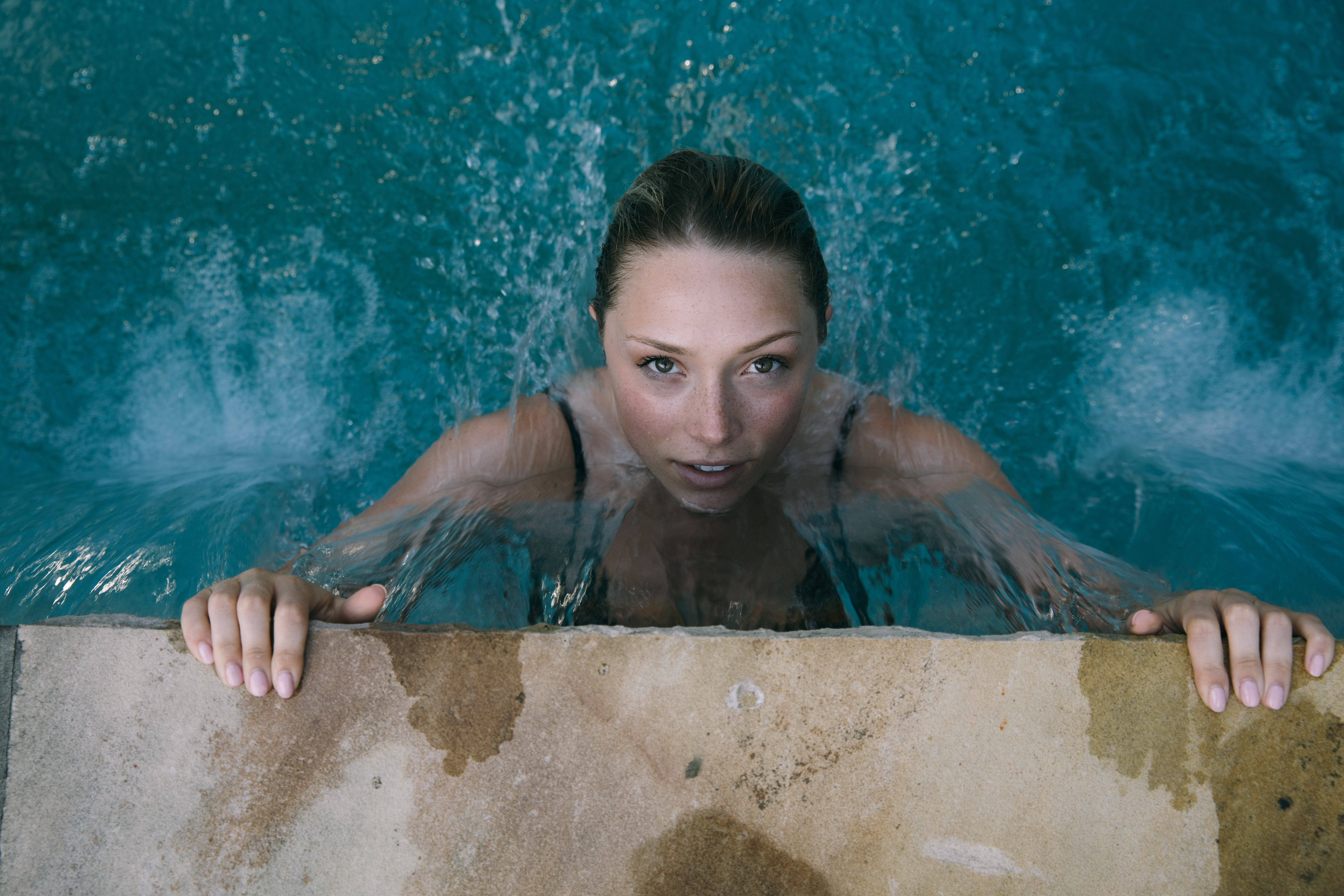 high-angle photo of woman in body of water holding on to brown concrete pavement
